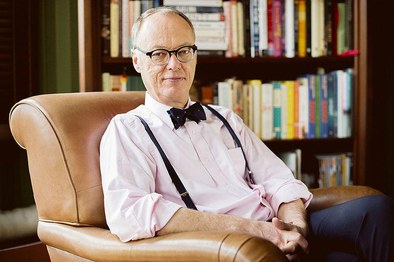 Christopher Kimball sits in a library`