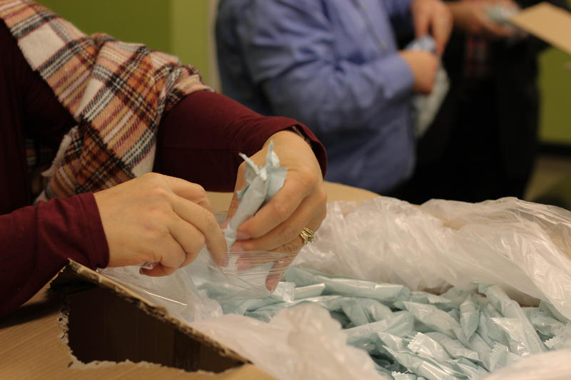 Volunteers at the Buren Shelter assemble bags of free tampons for shelter residents.