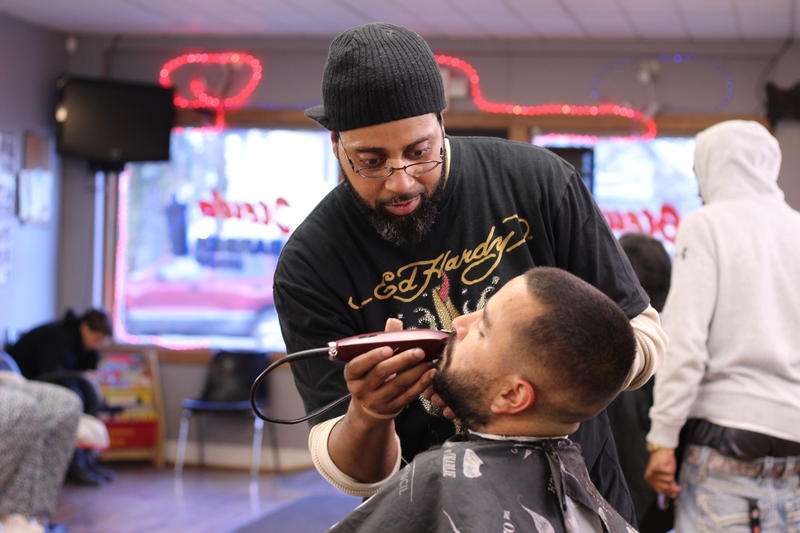 Armando McKnight is giving a client a cut at Stews barbershop on Sullivant Avenue.