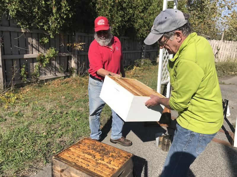 Beekeepers Larry Theurer (left) and Mark Vandayburg (right) are part of the Greater Cleveland Beekeepers Association. On a warm fall day, they peeked into a hive where bees were still hard at work.