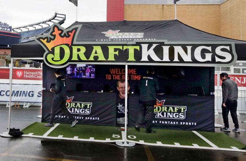 workers set up a DraftKings promotions tent in the parking lot of Gillette Stadium, in Foxborough, Mass., before an NFL football game between the New England Patriots and New York Jets.