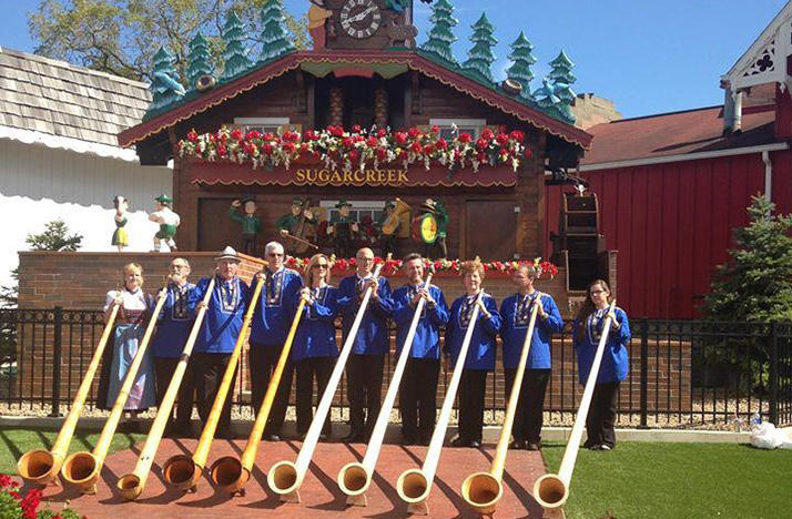 color photo of the members of Alphorn Grüezie standing with their alphorns in front of the Swiss clock in Sugarcreek, Ohio