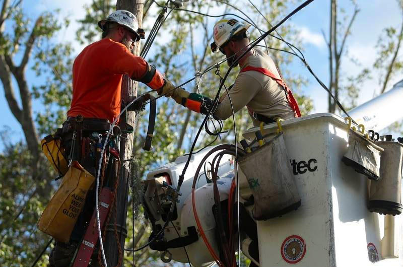 FirstEnergy utility workes repair a electric line damaged by a tree limb.