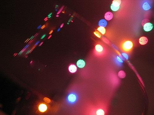 color photo of clear wine glass and multicolored Christmas lights
