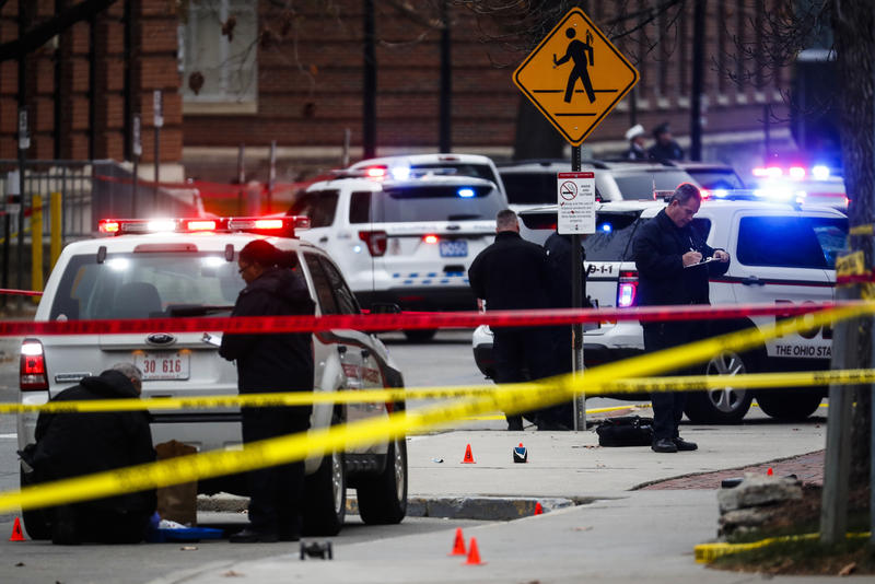 Crime scene investigators collect evidence from the pavement as police respond to an attack on campus at Ohio State University on Nov. 28, 2016.