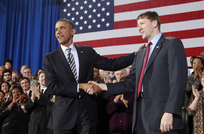 President Barack Obama shakes hands with Richard Cordray, in Shaker Heights, Ohio, in January 2012.