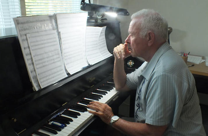 color side profile photo of David Del Tredici at the piano