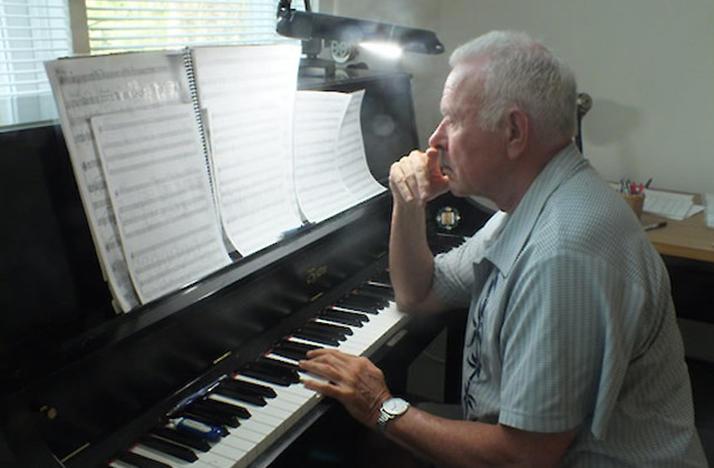 color side profile photo of David Del Tredici at the piano