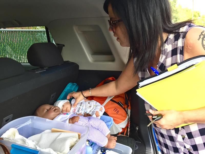 Nurse Elaine Patrick packs child-development and other educational materials into the back of her car. She visits new mothers and infants at home through the Help Me Grow Brighter Futures visiting nurse program.