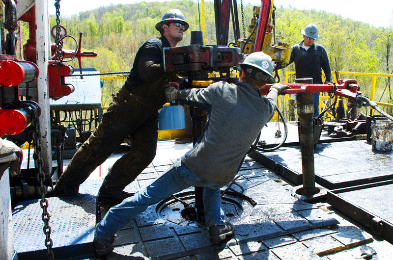 Workers move a section of well casing into place at a Chesapeake Energy natural gas well site near Burlington, Pa., in Bradford County.