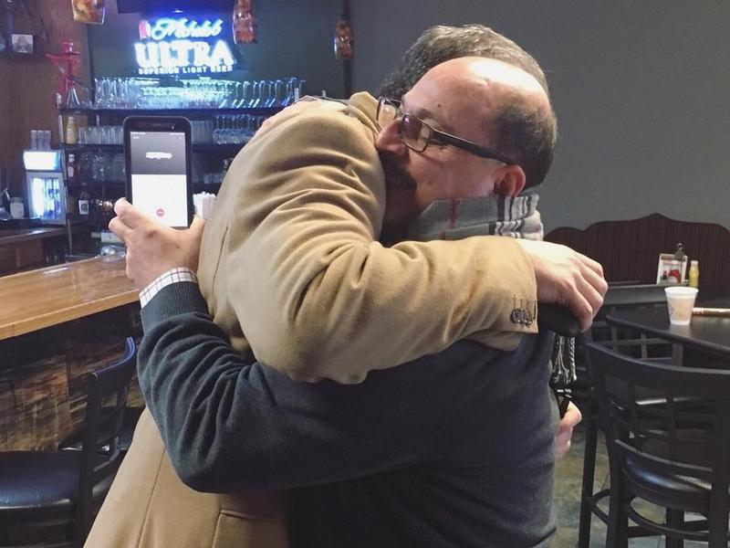 Amer Othman Adi and Congressman Tim Ryan embrace at the news of the deportation stay.