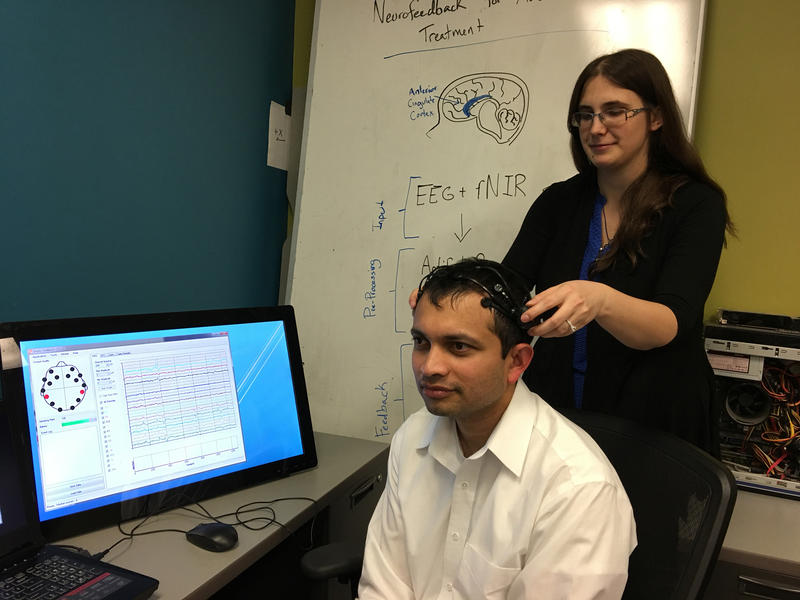 University of Dayton Research Institute software engineer Kelly Cashion (right) adjusts a wireless EEG headset on research engineer Nilesh Powar.