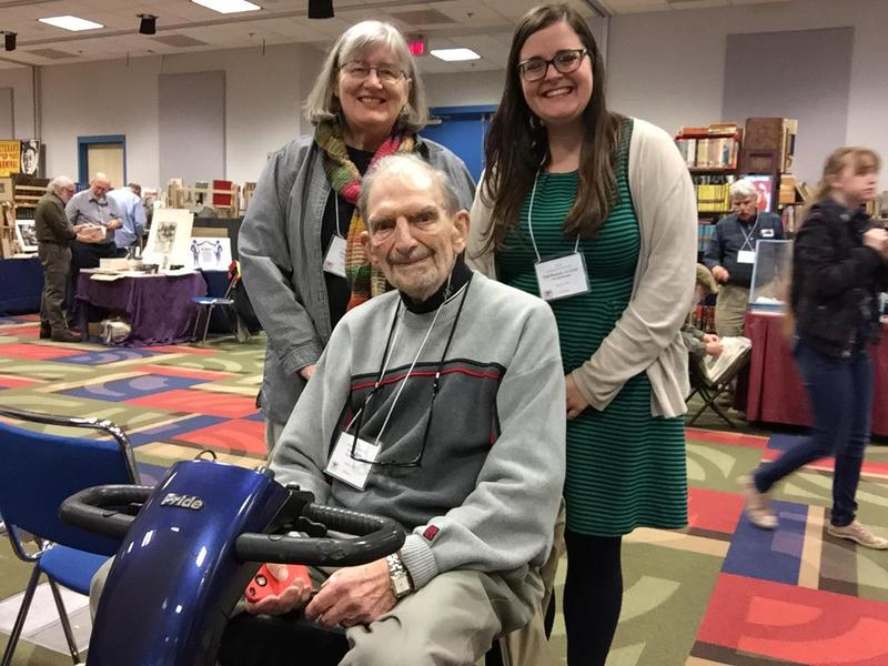 Frank Klein (seated) helped organize the first Akron Antiquarian Book Fair in 1983 at the Quaker Square Hilton. His granddaughter, Patti Russell (right), and her aunt, Andrea Klein, helped organize this year's show.