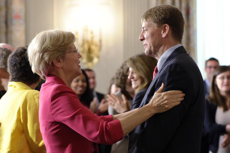 Elizabeth Warren talks with Richard Cordray in 2013.