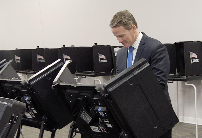 Secretary of State Jon Husted casts an early in-person absentee ballot at the Franklin County Board of Elections early voting center.