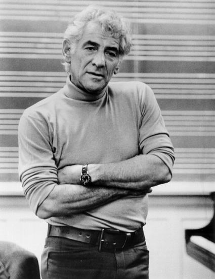 black-and-white photo of Leonard Bernstein standing in front of a blackboard with staff lines on it