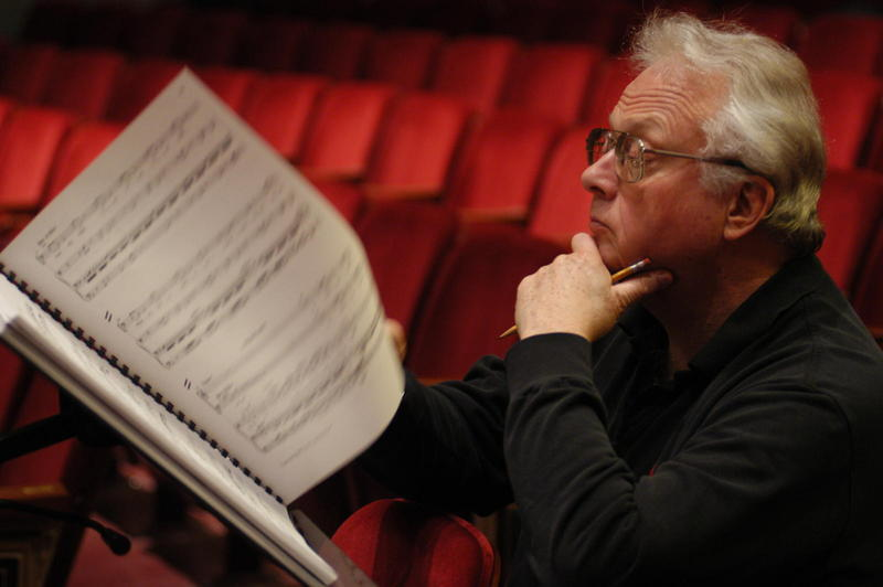 color photo of William Bolcom sitting in a theater and looking over a musical score