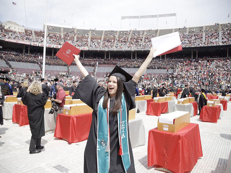 One of Ohio State's newest graduates celebrates receiving her degree at Ohio Stadium on Sunday.