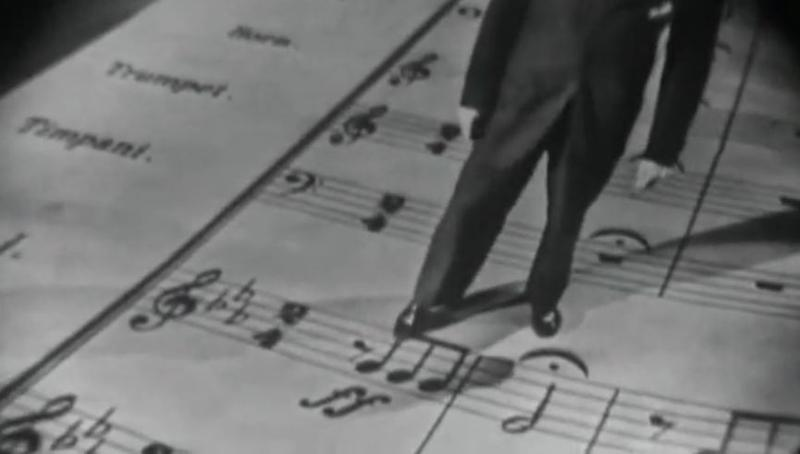 black-and-white photo of Leonard Bernstein pointing with his foot to notes on an oversized score of Beethoven's Fifth Symphony
