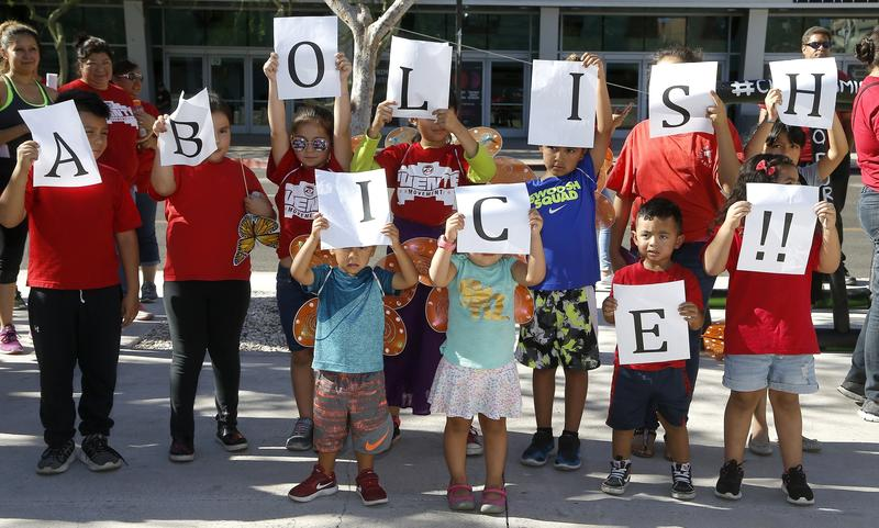 Kids hold up signs during an immigration family separation protest in front of the Sandra Day O'Connor U.S. District Court building, Monday, June 18, 2018, in Phoenix.