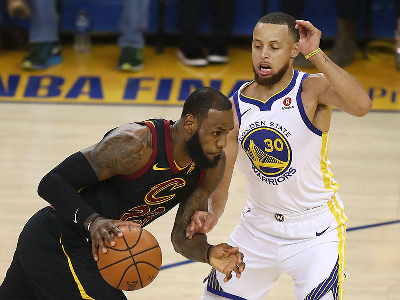 Cleveland Cavaliers forward LeBron James, left, drives against Golden State Warriors guard Stephen Curry during the first half of Game 1 of basketball's NBA Finals in Oakland, Calif., Thursday, May 31, 2018.