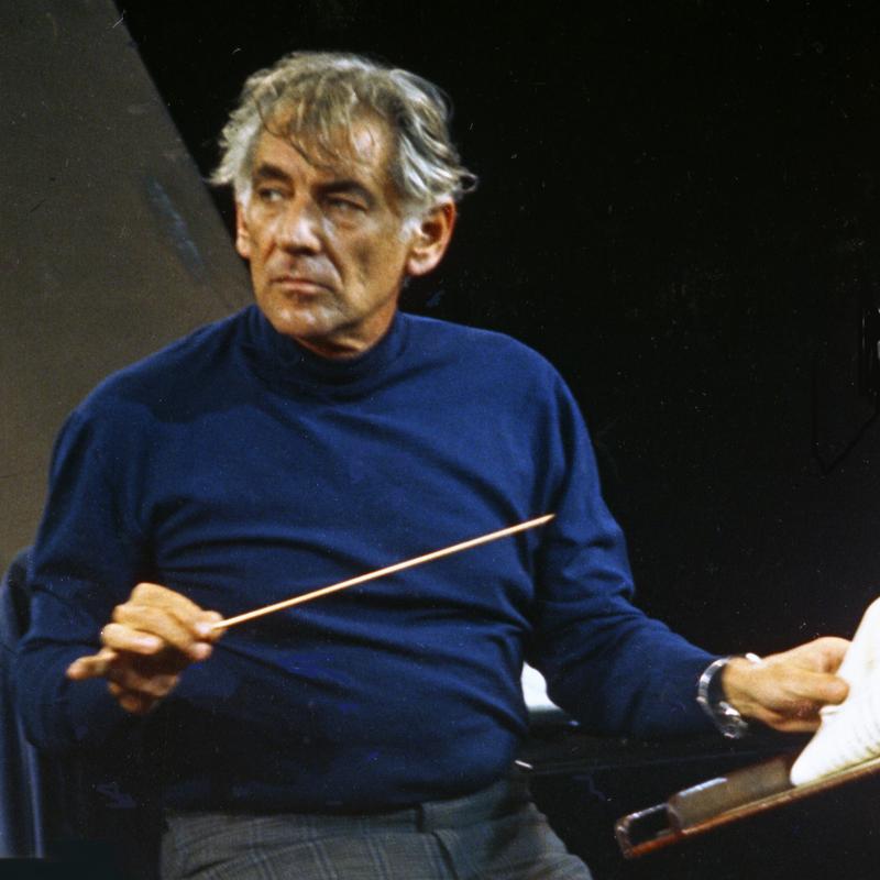 leonard bernstein in royal blue shirt holding conducting wand