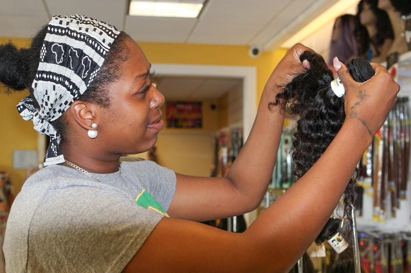 A customer at Ms. Melanin in Canal Winchester looks at a weave. Ms. Melanin is one of seven black-owned beauty supply stores in the state.