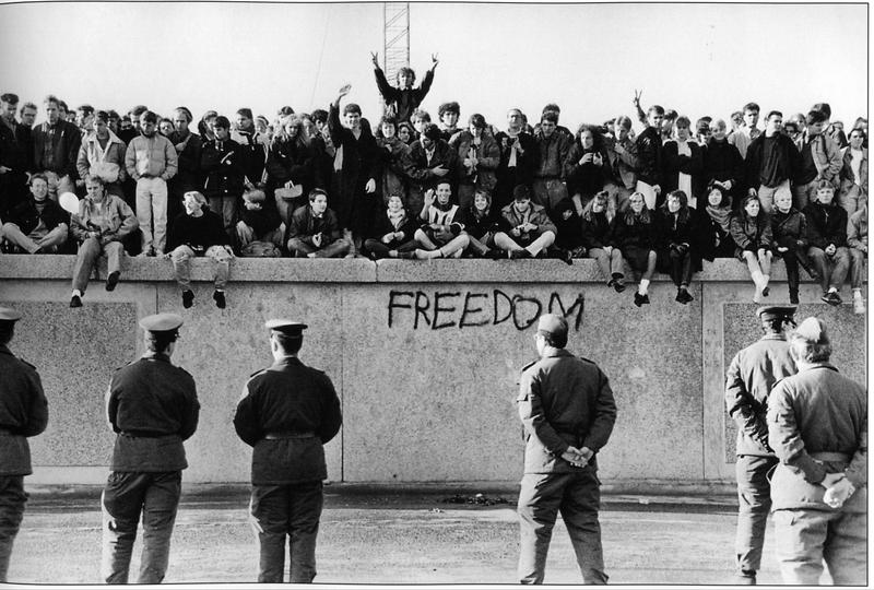 East German students sit on the Berlin Wall at the Brandenburg Gate in front of border guards in November 1989.