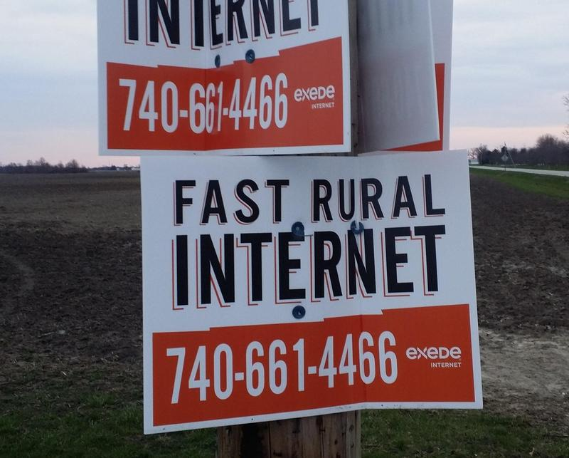 Signs in rural Fayette County advertise satellite-to-home internet service.