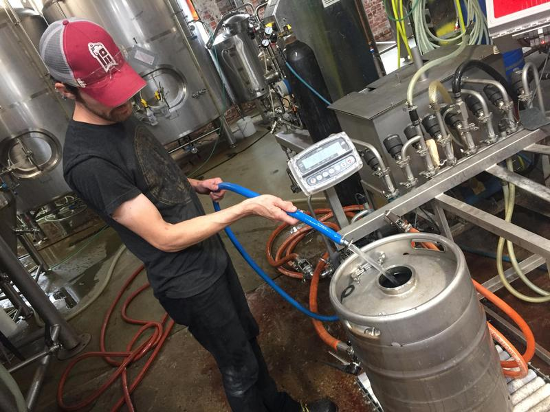 Workers prepare fora keg for a new batch of beer at Land Grant Brewing in Columbus.