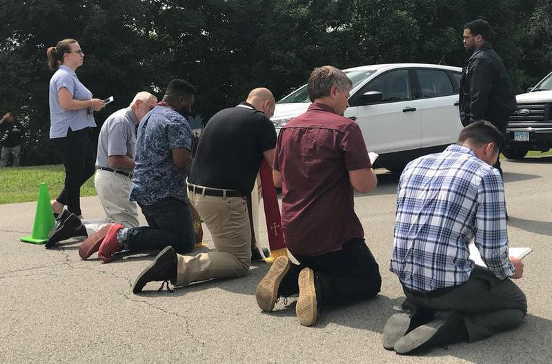 Protestors kneel at the Northeast Ohio Correctonal Center.