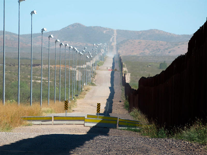 Stadium lights atop tall poles oversee a pedestrian barrier stretching for miles along a section of the border wall between Douglas, Arizona, and Agua Prieta, in the Mexican state of Sonora.