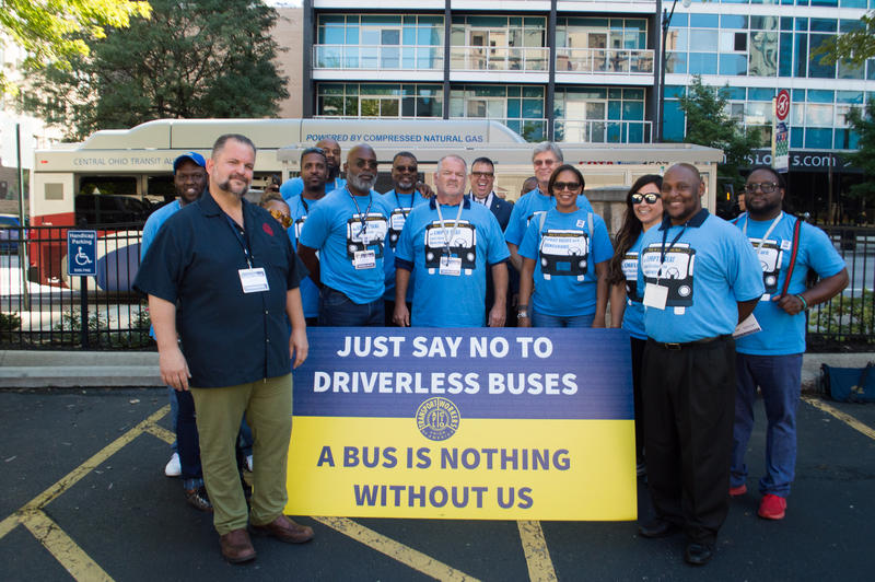 The Transportation Union of America stands in front of a bus stop on North Third Street to protest autonomous buses.