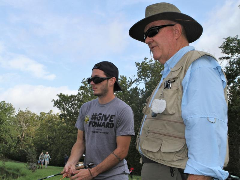 A volunteer for Projecting Healing Waters teaches a Columbus Crew player how to fly-fish.