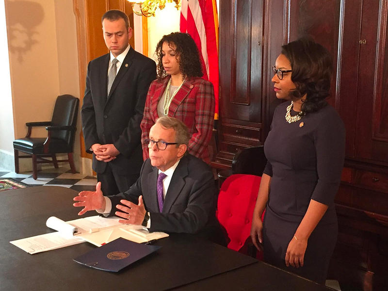 Ohio Gov. Mike DeWine discusses an executive order extending domestic violence protections as Sen. Nathan Manning (R-North Ridgeville), Rep. Janine Boyd (D-Cleveland Heights) and Rep. Emilia Sykes (D-Akron) look on.