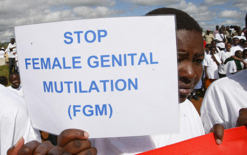A Masai girl holds a protest sign during the anti-Female Genital Mutilation (FGM) run in Kilgoris, Kenya, April 21, 2007.
