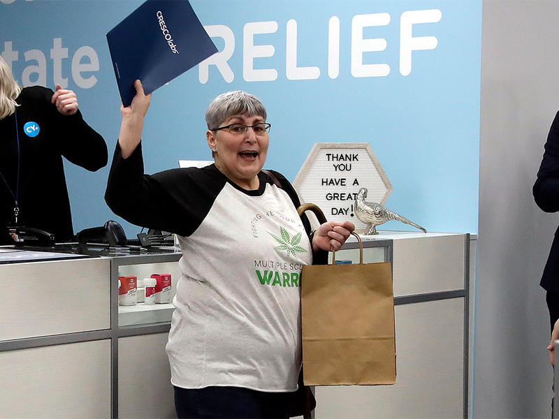 Joan Caleodis, of Martin's Ferry, Ohio, celebrates after making one of the first patient purchases of Ohio's Medical Marijuana program at Cresco Labs CY+ dispensary in Wintersville, Ohio, Wednesday, Jan. 16, 2019.