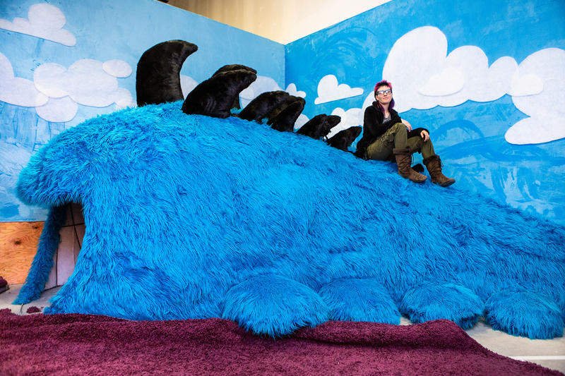 """Textile artist Hollie Hermes sits atop the """"sperm whale,"""" a large fuzzy creature that dominates one of the many rooms of Otherworld."""