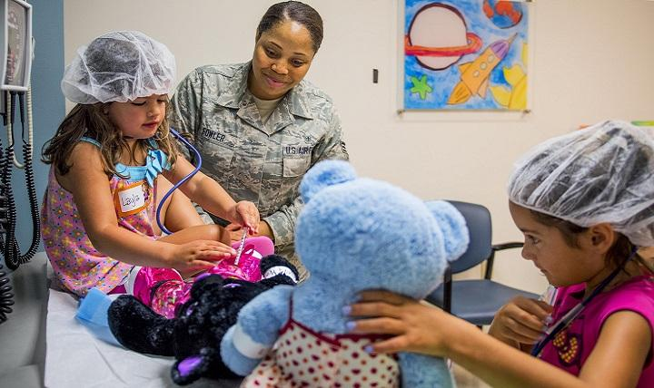 Air Force Senior Airman Antoinette Fowler shows a 4-year-old how to give a vaccination during a teddy bear clinic at Eglin Air Force Base, Florida.