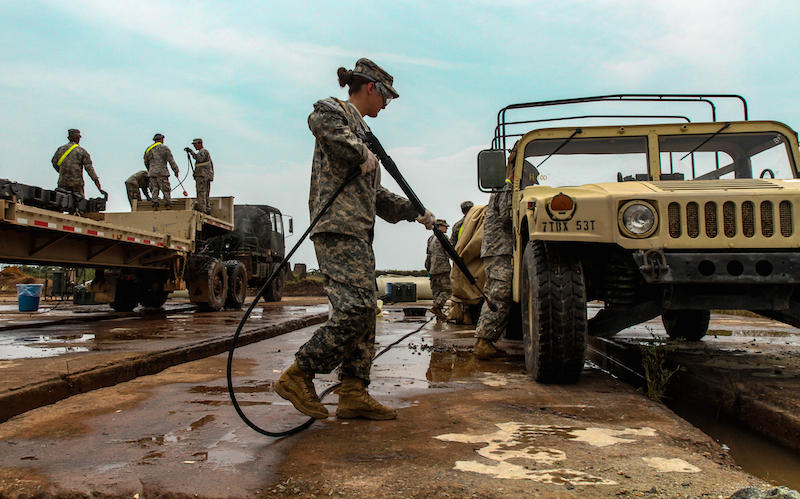 Soldiers with the 101st Sustainment Brigade wash their vehicles at an inspection point monitored by the United States Department of Agriculture prior to returning to the U.S.