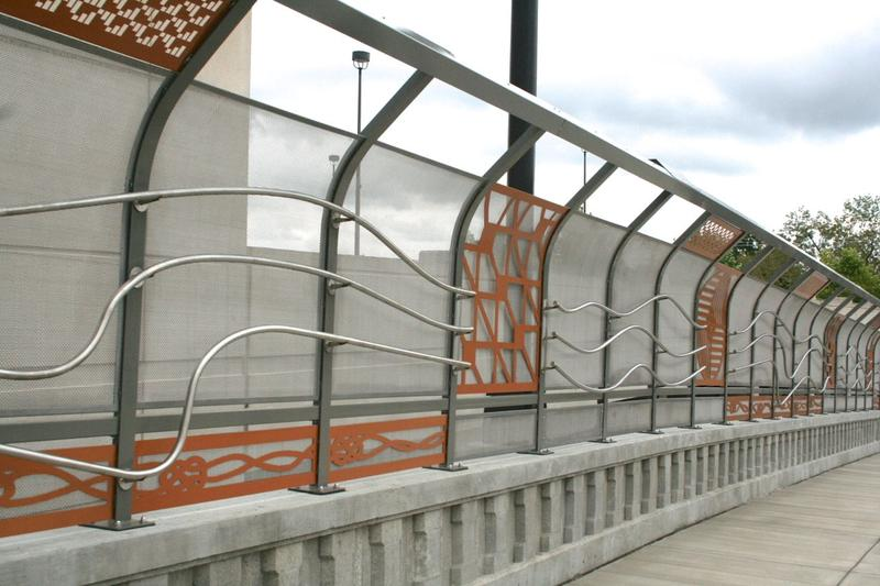 "In addition to the giant needle, David Dahlquist's ""Thread and Needle"" forms the railings on either side of the 28th Avenue Connector bridge. It's panels symbolize bringing together two communities long separated by race, custom and economic status."
