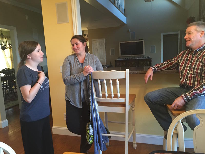 Maggie Hall, left, and her parents talk in their home near Cookeville in 2015, just after they were accepted into the Undiagnosed Diseases Network.