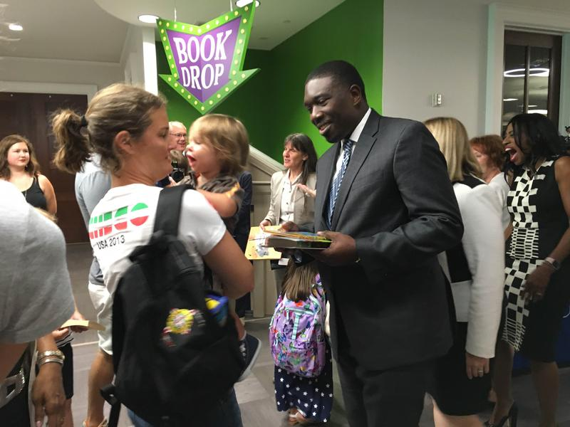 Superintendent Shawn Joseph hands out books to children at his first press conference, in July, on childhood literacy.