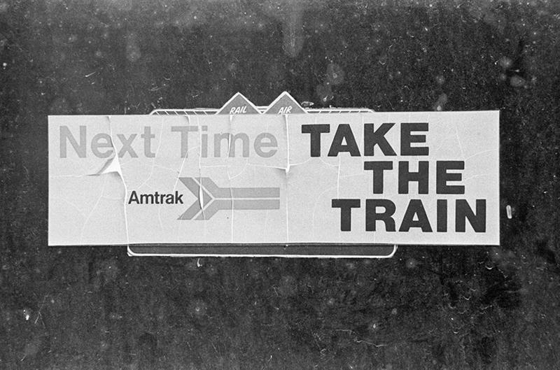A cracked a peeling sign contradicts the spirit of the message. Photographer Jay Mather says perhaps it symbolizes Amtrak's larger problems with old equipment and worn track.