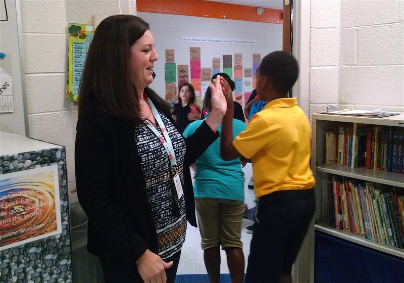 Jennifer Burnell high-fives students as they leave her classroom at Fall-Hamilton Elementary School.