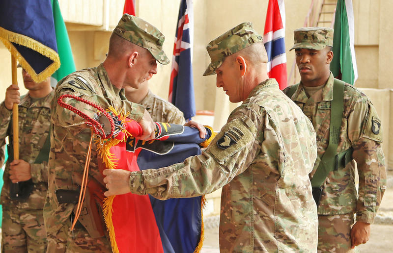 """During a formal """"Transfer of Authority"""" ceremony in Baghdad, Maj. Gen. Gary Volesky rolls up the 101st Airborne flag. Hundreds of soldiers have been in Iraq since February on what was called an """"advise and assist"""" mission."""