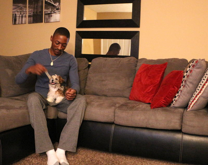 De'Anton Gipson plays with his puppy, Mariah, in his apartment in Murfreesboro.