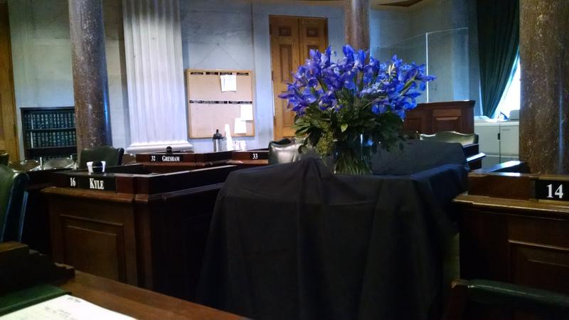 The desk in the Senate chamber used by Douglas Henry is draped in black cloth and decorated with irises, the state flower.