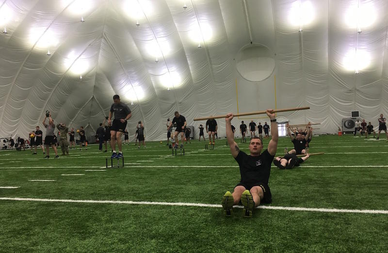 101st Aiborne officers did a morning workout in the Titans indoor field before meeting with business executives.