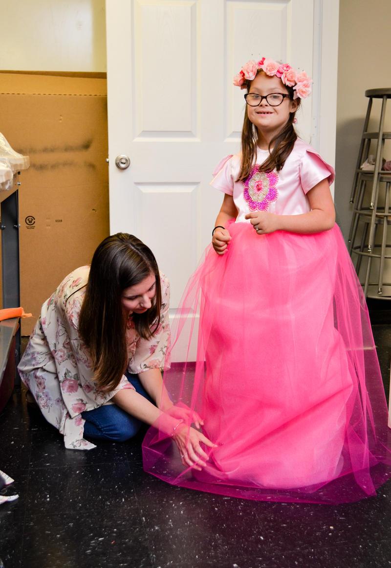 A shy princess gets her dress hemmed.